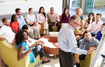 Image of employees sitting in circle during brainstorming session